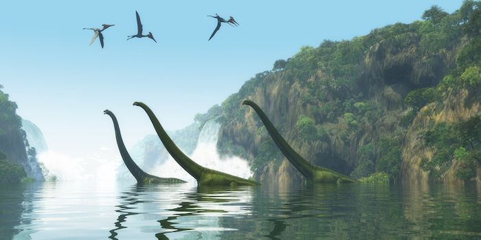 Two Mamenchisaurus dinosaur adults escort a youngster across a river as Pterodactylus birds search for fish prey. By Catmando | Shutterstock.com